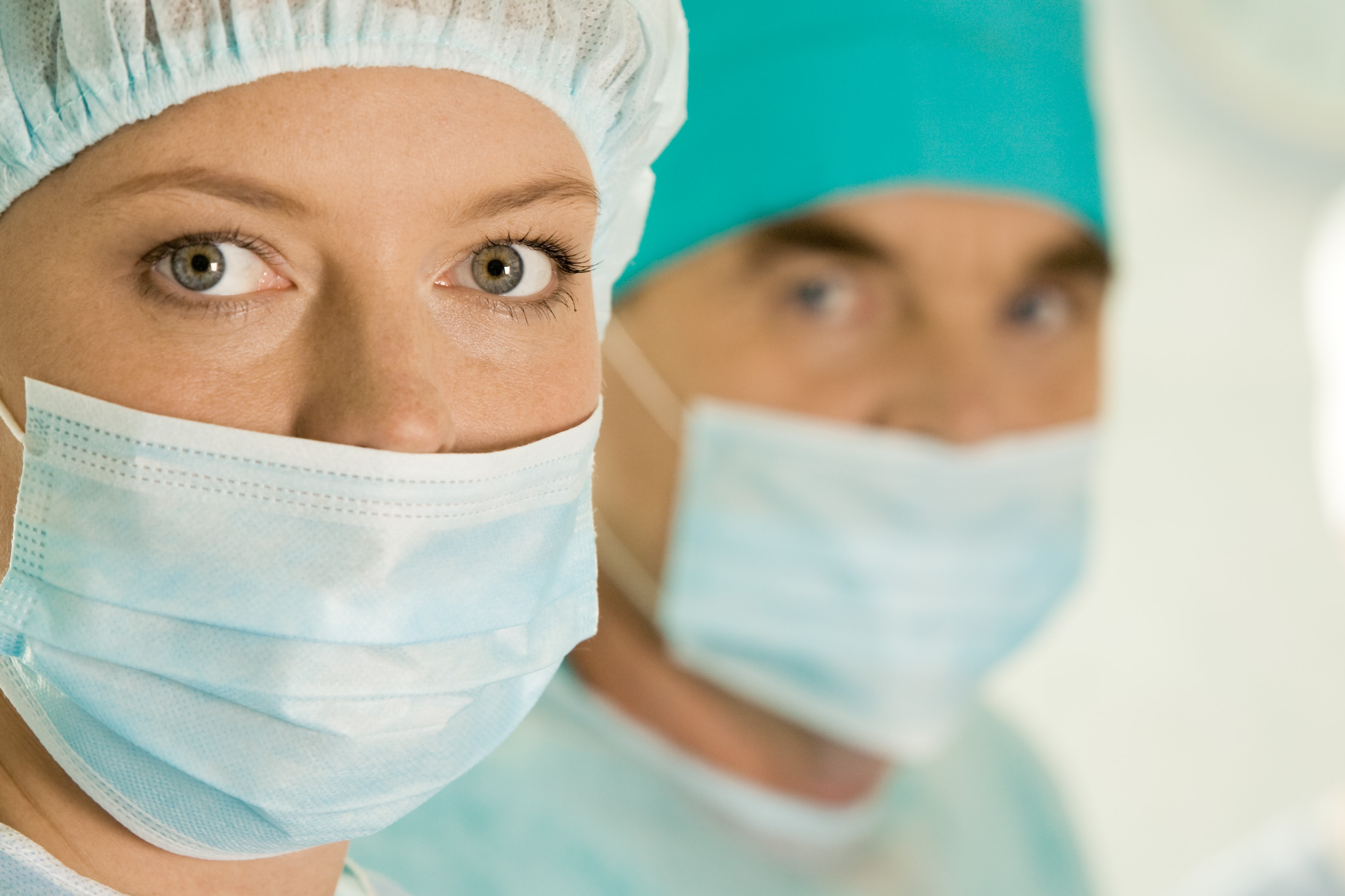 Portrait of female surgeon wearing protective mask on background of her colleagues